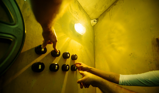 In-game: Promo images of 3 hands manipulating a matrix of 8 light switches.