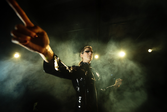 In-game: Promo images of a Matrix-y looking cyber punk woman in black leather and and sunglasses. She is lit and gesturing dramatically.