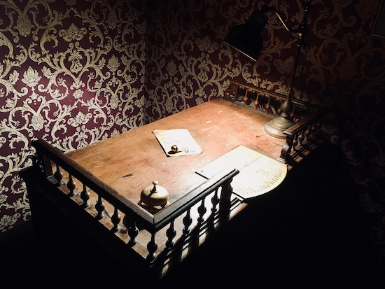 In-game: A wooden bellhop's desk with a bell and a note.