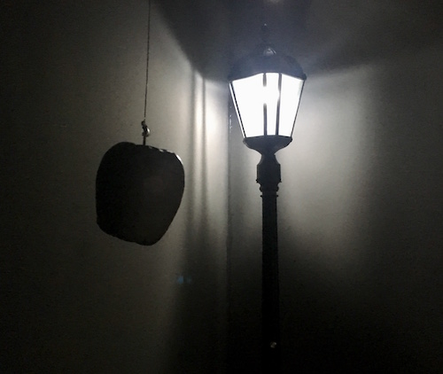 In-game: A glowing street lamp with an apple hanging in front of it by a fishing line.