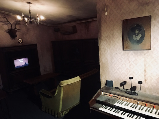 In-game: A grim and rundown living room with an old dusty synthesizer.
