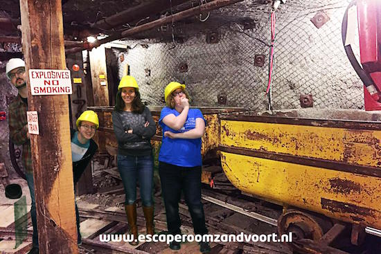 Post game green screen photo of the team beside mining carts. David and Lisa are peaking out from behind a post.