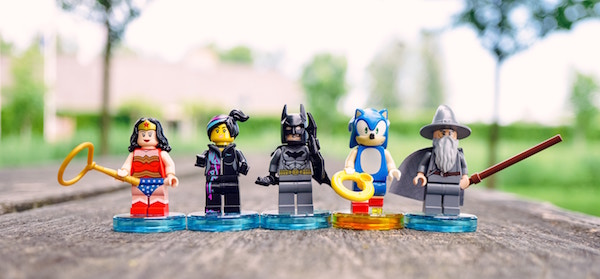 Lego Wonder Woman, Batman, Sonic, and Gandalf figures standing on a road outdoors.