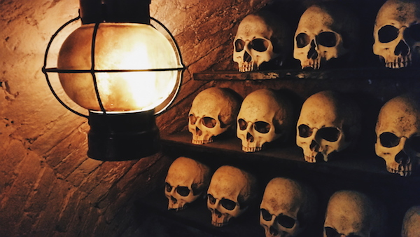 In-game: a wall of human skulls lit by a lantern.