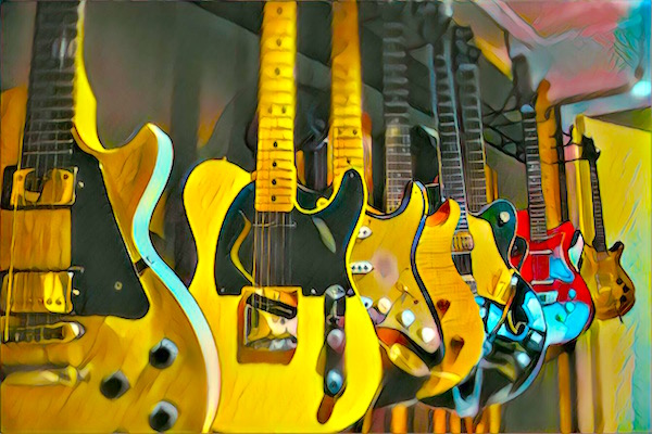 A collection of guitars including a Gibson Les Paul, Fender Stratocaster, and Fender Telecaster.