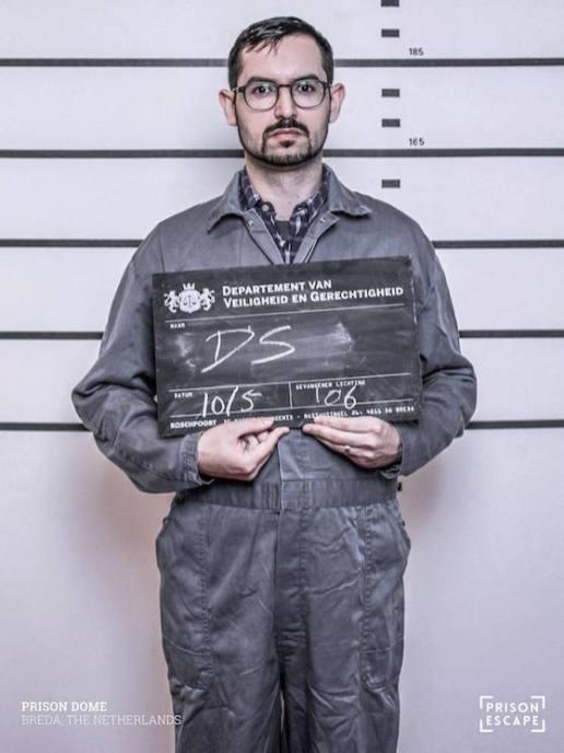 David's Prison Escape mugshot in an grey jump suit.
