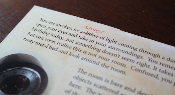 "The interior of the card shows edits in read, ""slither"" is crossed off and rewritten as ""sliver."" An extra period is added to complete an elipsis."