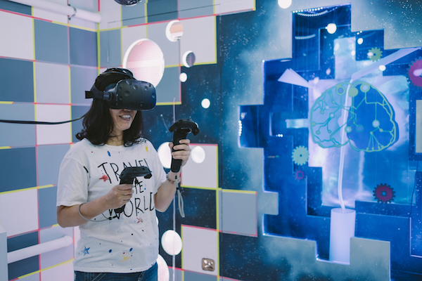 Un-Destined - Someone wearing a VR kit in space-y escape room like setting.
