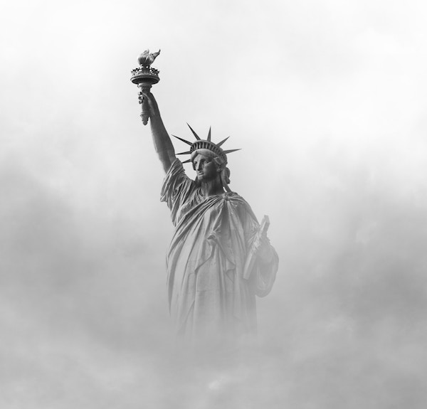 The Statue of Liberty in black & white, immersed in fog.