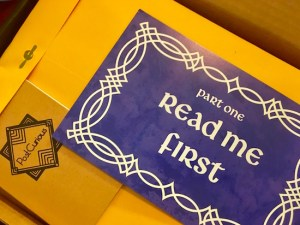 """A manila envelope, a small Post Curious notebook, and a blue letter that reads """"Part One Read Me First."""""""