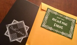 "A green letter that reads ""Part Two Read Me First,"" atop a sealed manila envelope and the Post Curious box."