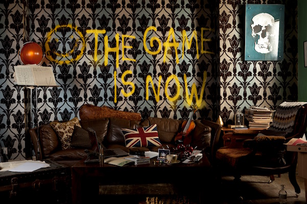 "The living room of Sherlock's cluttered London flat. The wall is graffitied, ""THE GAME IS NOW."""