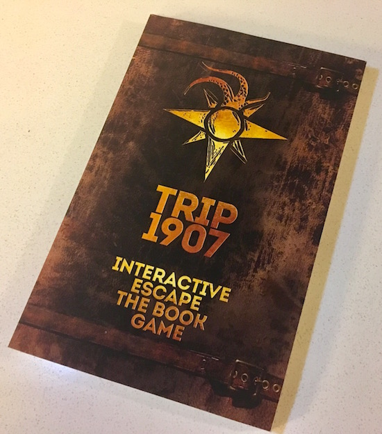 The faux leather cover of Trip 1907: Interactive Escape The Book Game features a gold compass rose with tentacles emerging from North.