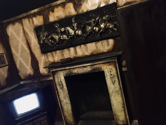 In-game: an old rundown and weathered living room with a fireplace and CRT television.