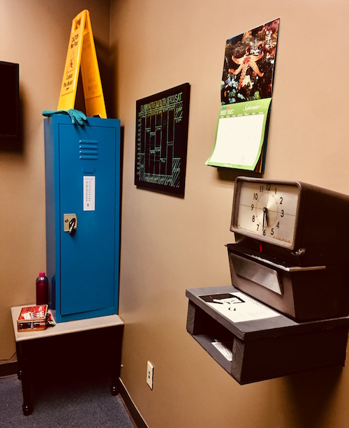 In-game: an employee breakroom with a locker, schedule, calendar, and a clock in/out machine.
