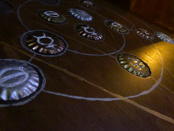In-game: A wooden table with strange medallions mounted to it.