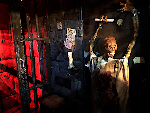 In-game: A dungeon with a dead body gripping a scroll mounted to the wall.