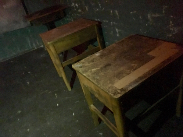 In-game: a series of old school desks in a dark, grim room.