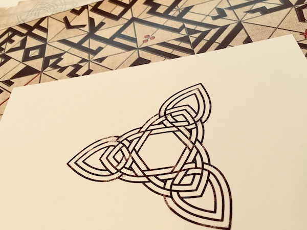 In-game: A card with a complex knot pattern, on top of an unusual paper maze of some sort.