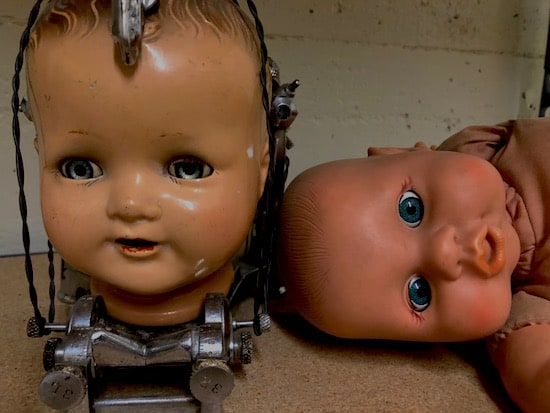 In-game: Creepy doll heads in metal contraptions.