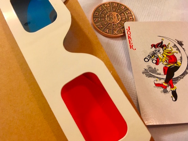 Red/blue 3D glasses, a cipher coin, and a joker card.