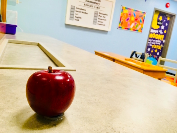 In-game: A red apple sitting on the teachers desk in front of the classroom.