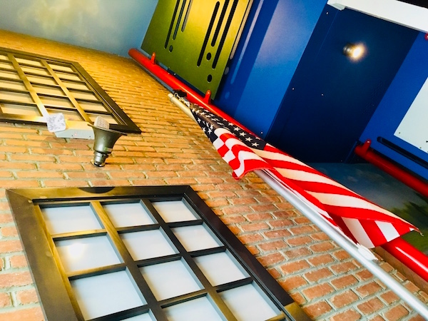 In-game: The exterior of the school building with a PA and American flag.