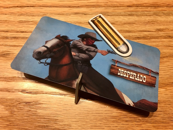 A desperado card with a card stock base knocked over by a card stock bullet.