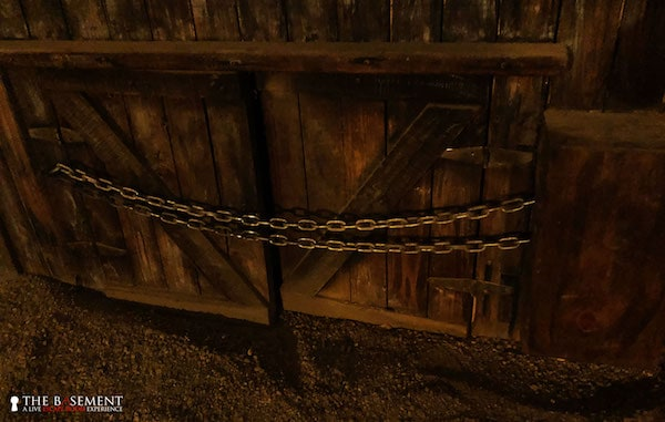 In-game: heavy wooden doors chained shut.