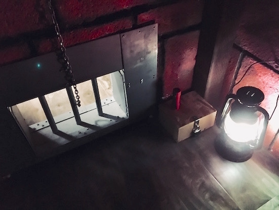In-game: a glowing lantern, flashlight, and lockbox next to a small barred passageway with a chain running through it.