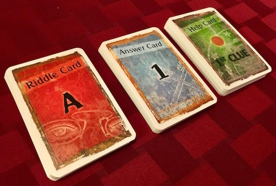 The riddle cards, answer cards, and help cards decks.