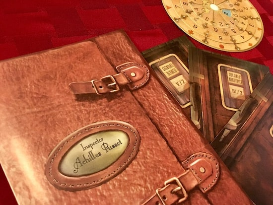 The notebook of Achilles Pussot, an answer wheel, and three train compartment components.