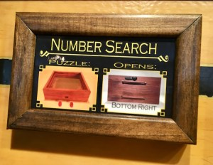 """In-game: a framed puzzle description labeled """"Number Search."""" It shows the puzzle component and the box that it opens."""