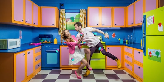 Claustrophobia game promo: a couple catching cupcakes in a unusual, brightly colored kitchen