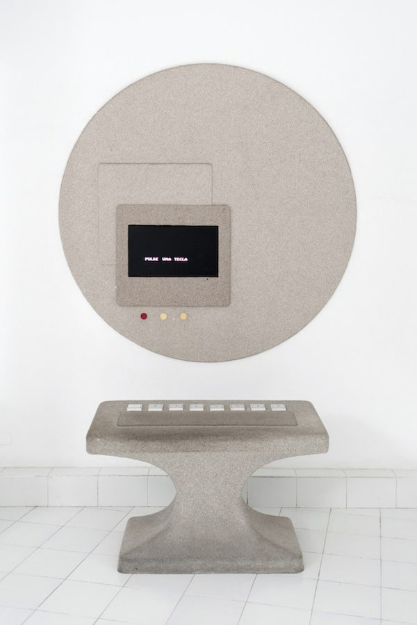 A strange geometric concrete pedestal with 8 buttons below a circular screen.
