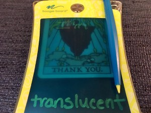 "A small translucent boogie board with card under it that reads ""Thank You,"" with tarot art. Atop, the boogie board reads, ""I'm translucent."""