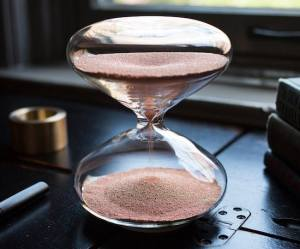 A beautiful glass hourglass with copper ballbearings inside as sand.