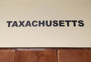 """In-game: the word """"Taxachusetts"""" painted boldly on the wall."""