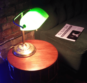 In-game: A lamp illuminating a couch with a newspaper.