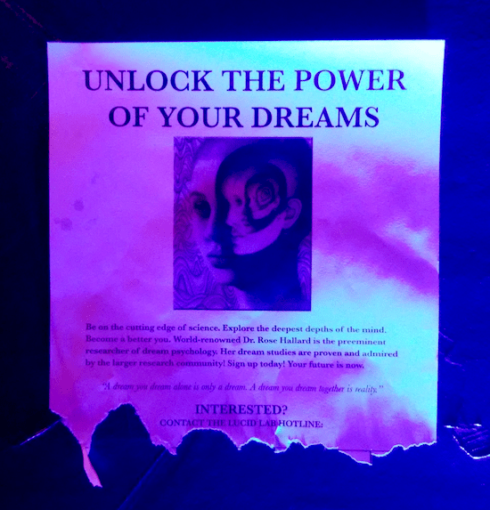 "In-game: A poster telling the reader to ""Unlock the power of your dreams."" It has a trippy image of heads within heads."