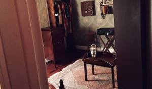 In-game: View through the door of Do Not Disturb into a studio apartment with a creepy doll sitting on a table in the middle of the room.