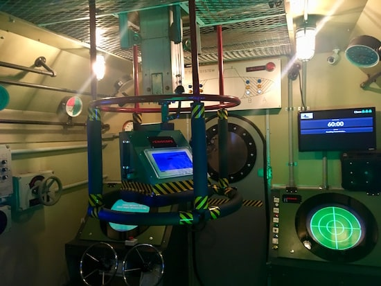 In-game: The bridge of the submarine. A sonar station and periscope are in view.