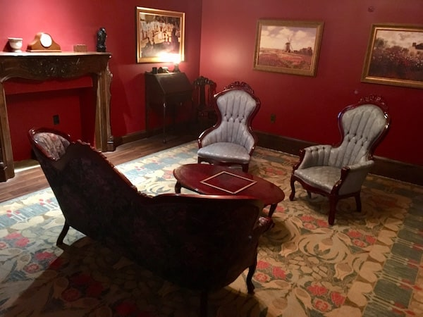 In-game: An old parlor with large antique furniture, deep red walls, and large framed paintings.