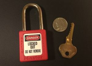 Red Master Lock 410 beside its brass key and a quarter for size reference.