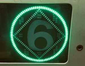 A glowing green 6 train sign.