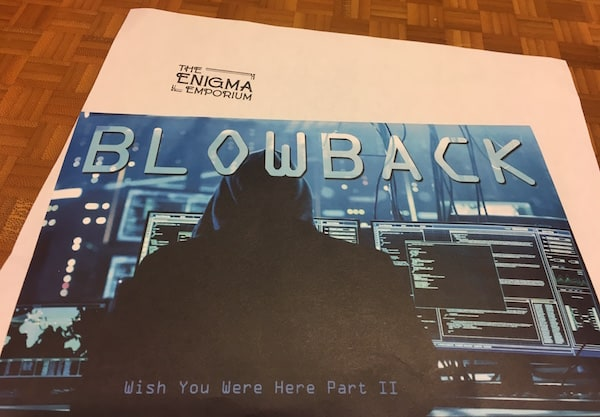 """The """"Blowback: Wish You Were Here Part II"""" envelope depicts a black hoodied hacker in front of many computer monitors."""