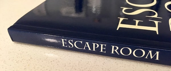 "The binding of the navy blue journal reads ""Escape Room."""