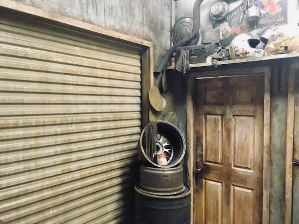 The exterior entrance/ exit for The Garage. A weathered door and garage door surrounded by car parts.