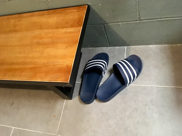 In-game: flip flops on the floor beside a bench.