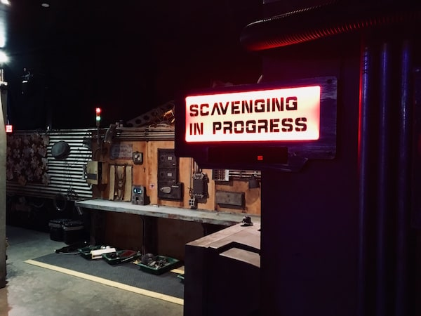 """In-game: A scrapyard with a red sign reading, """"Scavenging in Progress"""""""